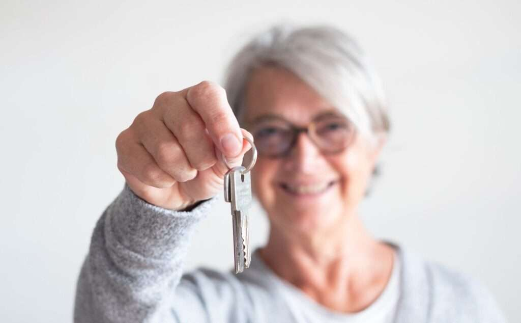 close up of mature woman holding a couple of keys of her new house or home or some property